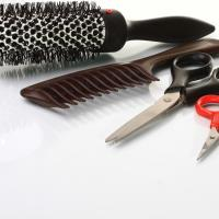 Beautician tools featuring hair brush, comb and scissors.